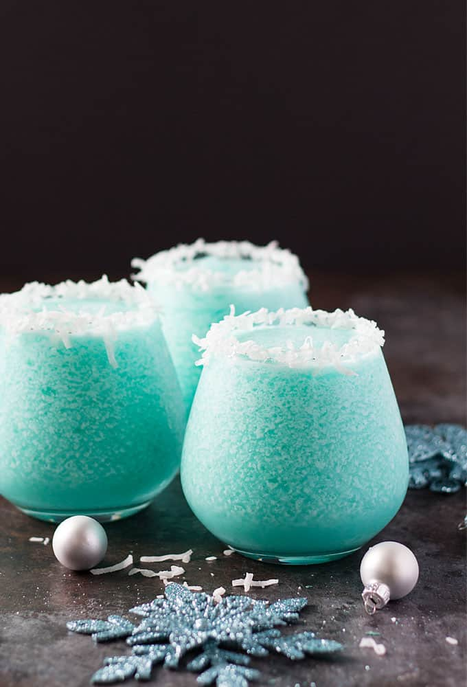 Three blue frozen cocktails in glasses rimmed with flaked coconut.