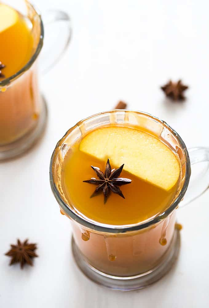 A hot toddy in a mug with caramel syrup around the rim, an apple slice and star anise.