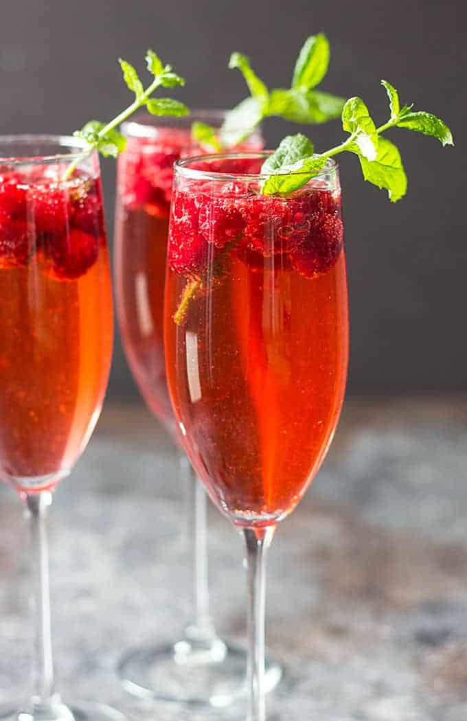 Champagne rum punch in three flutes with raspberries and fresh mint sprigs.
