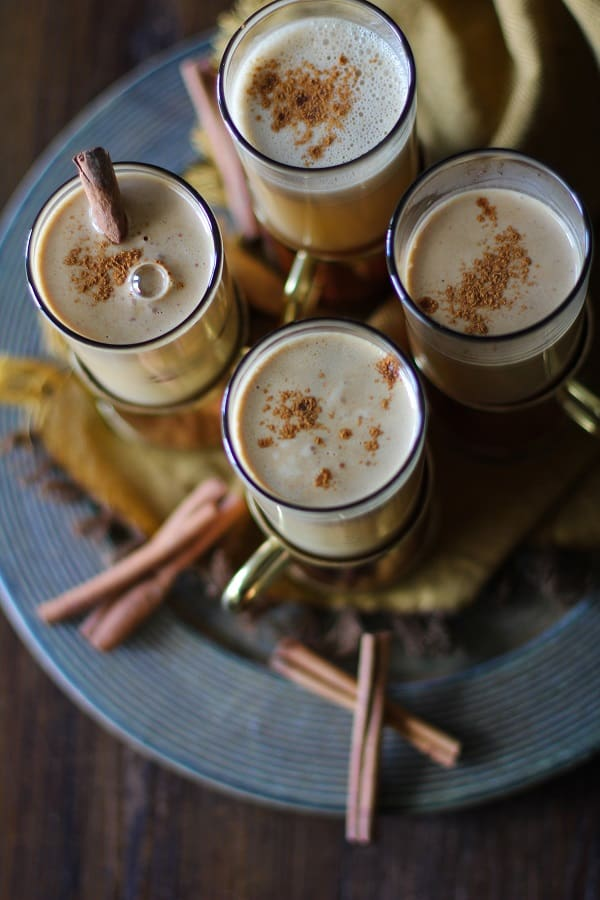 Overhead view of four mugs of hot buttered rum cocktails on a serving platter.