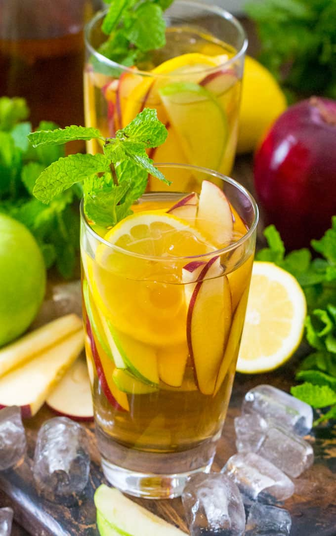 An iced tea cocktail in a glass with sliced apples, lemon and fresh mint.