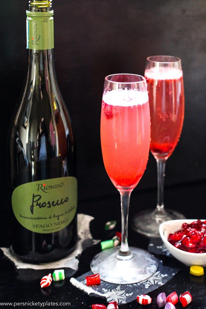 Two champagne flutes of cranberry sparkling wine cocktails beside a bottle of prosecco.