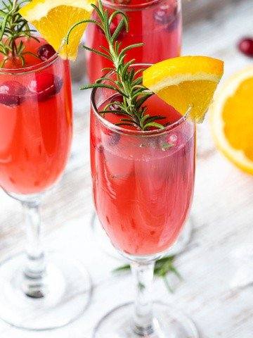Three mimosas garnished with rosemary, cranberries and an orange slice.