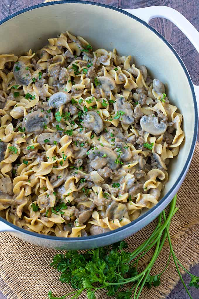 Overhead view of ground beef stroganoff with mushrooms in a white dutch oven.