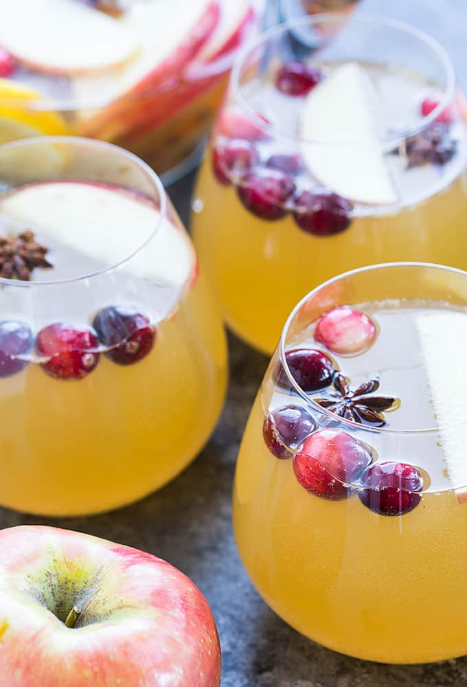 Three glasses of sangria garnished with cranberries, sliced apple and star anise.