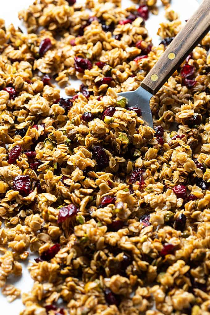 Closeup of granola on a baking sheet with a wooden handled spatula.