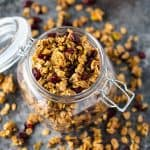 Overhead view of homemade granola in an opened glass canister.