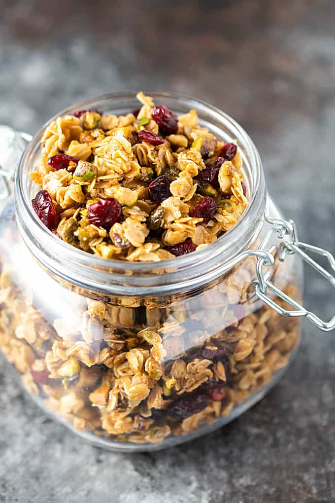 Granola with dried cranberries and pistachios in an open glass canister.