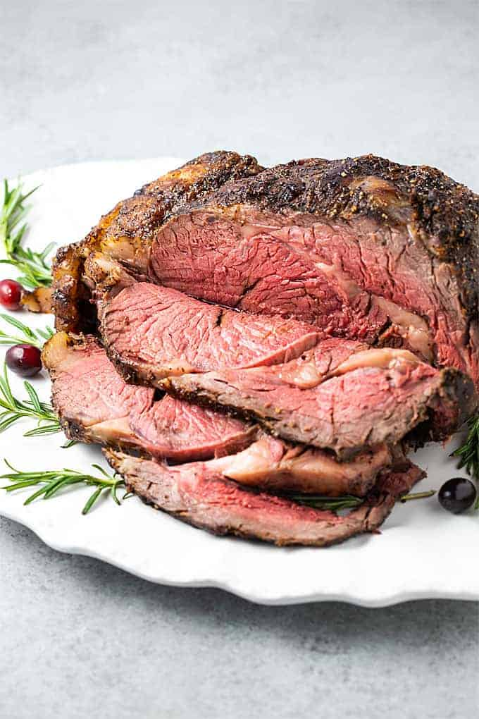 A sliced boneless prime rib on a white serving platter garnished with fresh rosemary and cranberries.