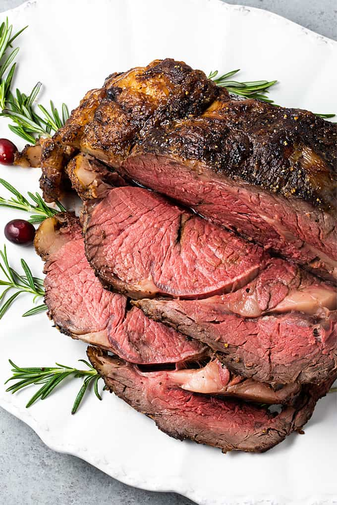 Overhead closeup of a partially carved prime rib roast on a white serving platter.