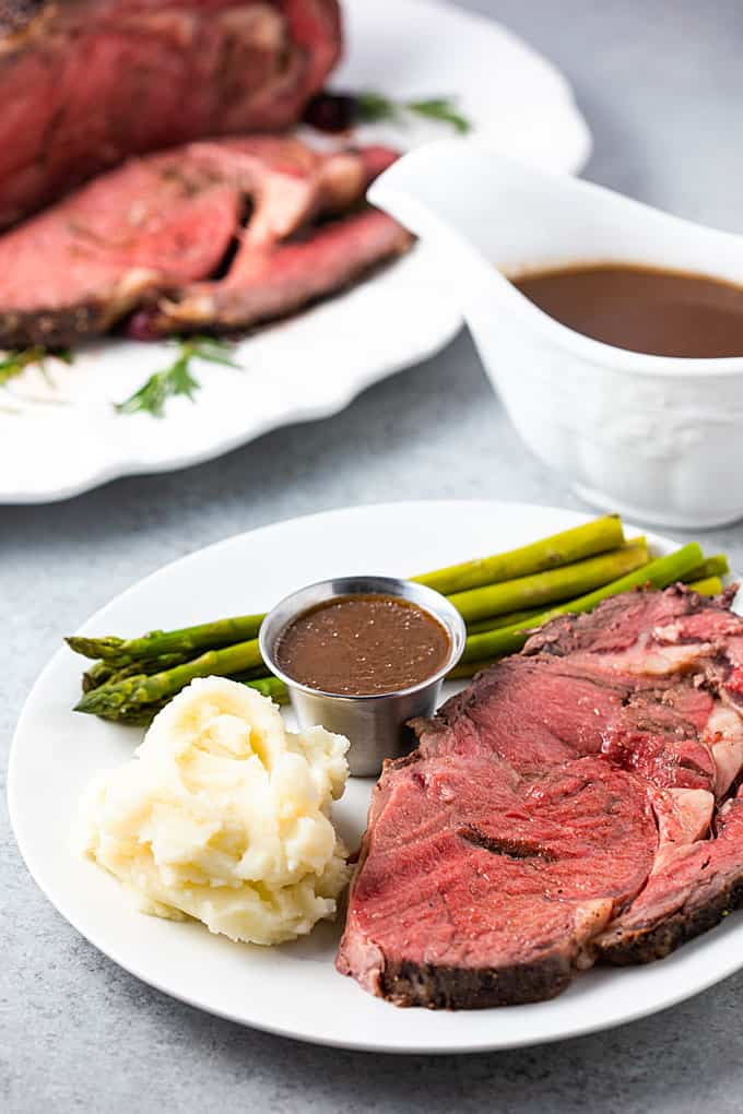 A slice of prime rib on a white plate with mashed potatoes, asparagus and au jus.