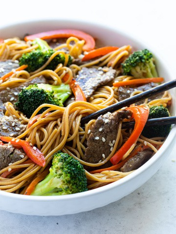Beef and Broccoli Lo Mein in a white bowl with chopsticks.