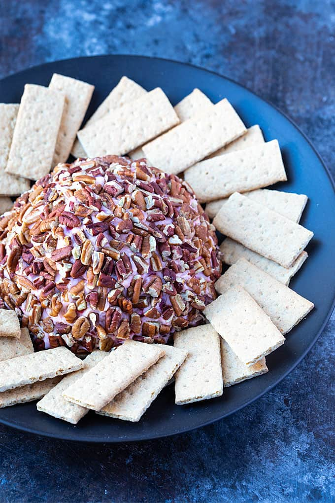 Cherry Cheese Ball on a black plate with a cheese knife and graham crackers.