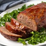 Sliced Classic Meatloaf on an oval white platter with parsley and a denim napkin.
