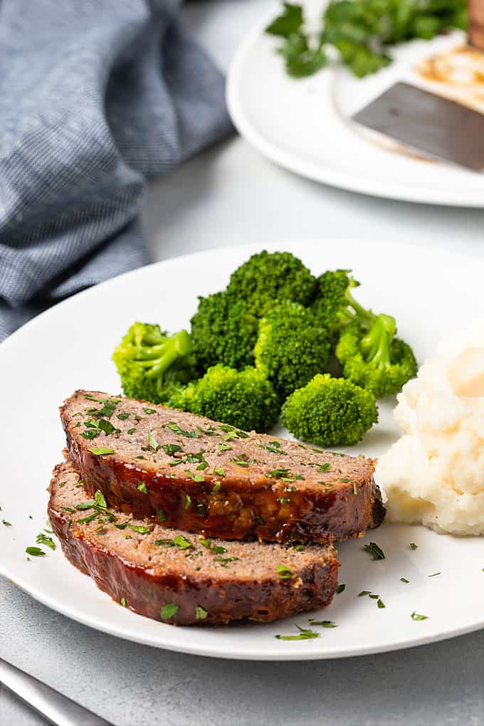Two slices of meatloaf on a white plate with broccoli and mashed potatoes.