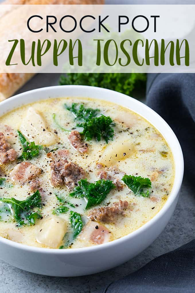 Crock Pot Zuppa Toscana soup in a white bowl with French bread and a dark grey napkin.