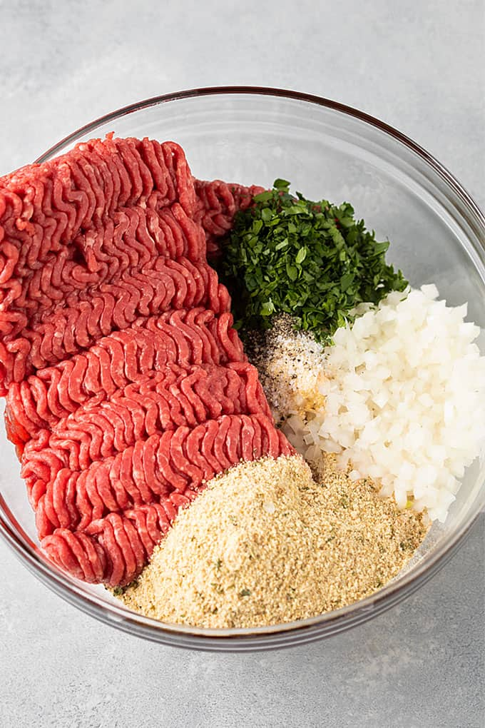 Meatloaf recipe ingredients in a large clear bowl (ground beef, bread crumbs, onion, fresh parsley and seasonings).