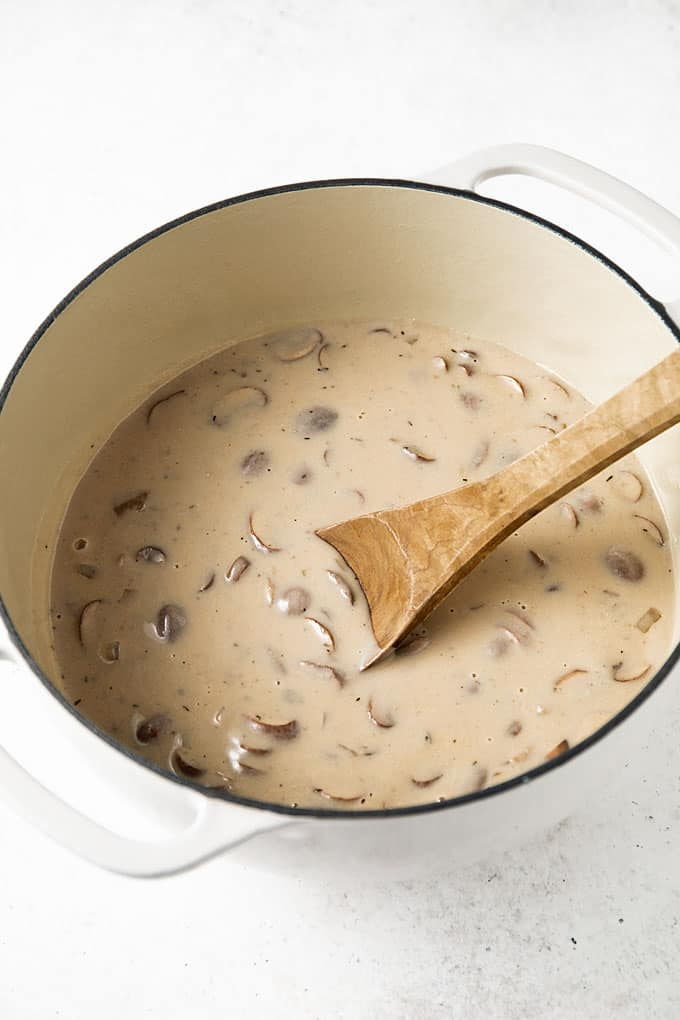Cream of mushroom soup in a white dutch oven with a wooden spoon.