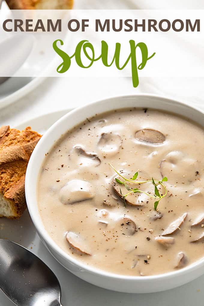 Cream of mushroom soup in a white bowl on a plate with a spoon and a slice of French bread
