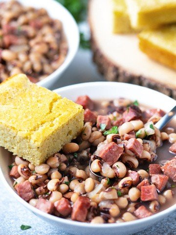 Black-eyed peas and ham in a white bowl with a spoon and a slice of cornbread.