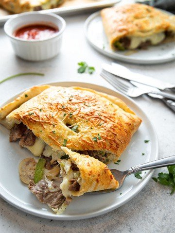 Two philly cheese steak calzones on white plates with 2 forks, 2 knives and a side of marinara sauce.