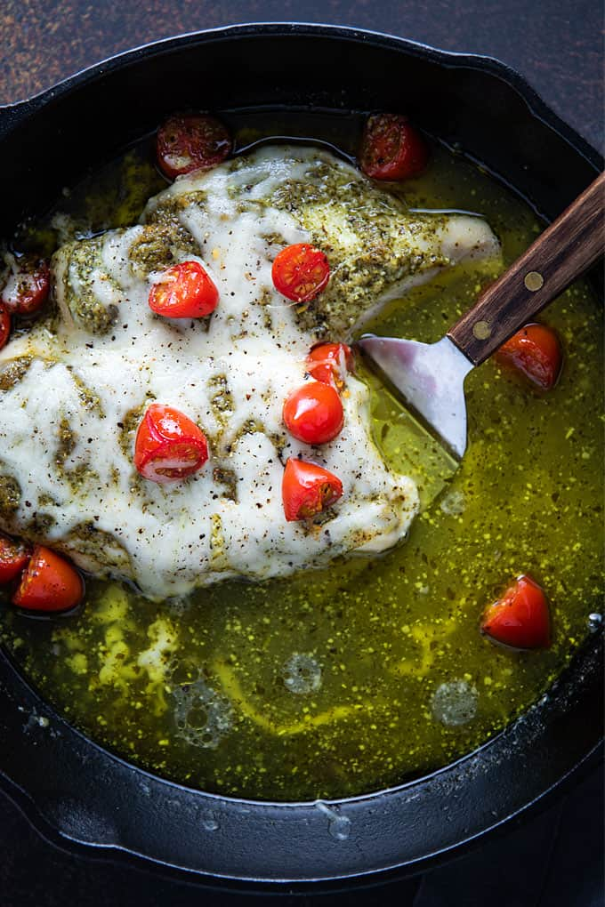 Baked pesto chicken topped with melted provolone cheese and cherry tomatoes in a cast iron skillet.