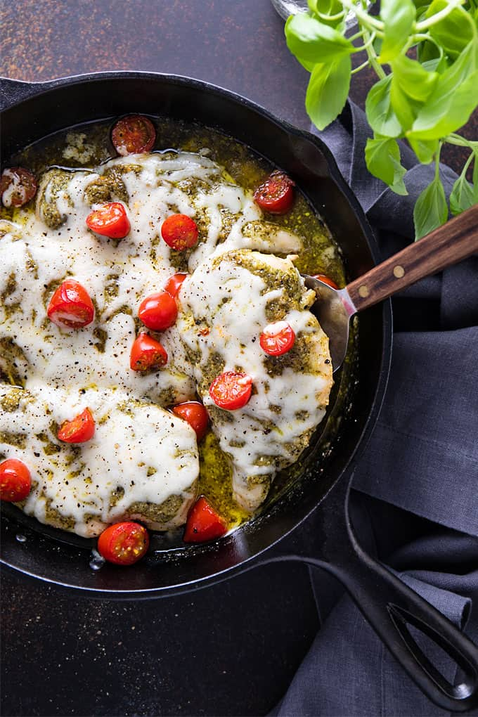 Overhead view of pesto chicken bake in a cast iron skillet.