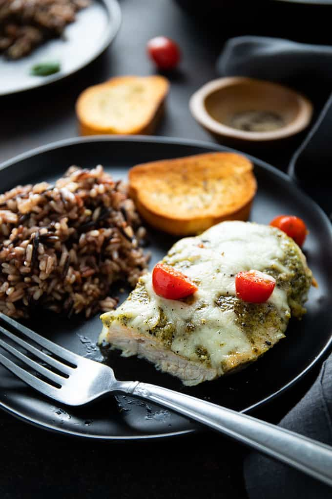 Baked pesto chicken topped with provolone cheese and tomatoes in a black plate with wild rice and a slice of French bread.