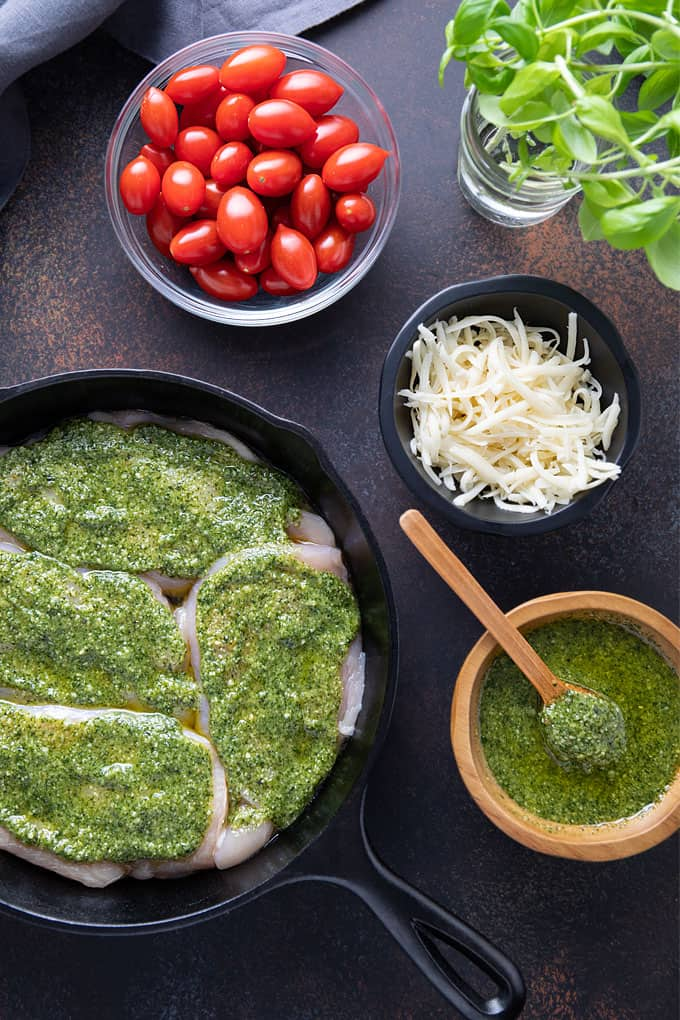 Ingredients for baked pesto chicken: 4 boneless chicken breasts, pesto, shredded provolone cheese and cherry tomatoes.