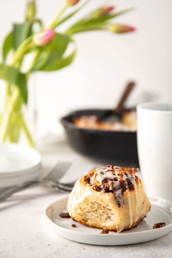 A cinnamon roll on a small round plate beside a cup of coffee and 3 forks.