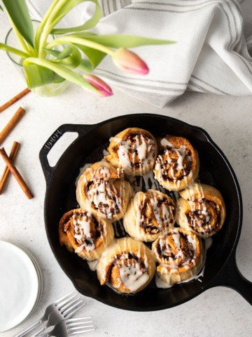 Glazed cinnamon rolls in a cast iron skillet beside a stack of small round white plates, cinnamon sticks, a vase of pink tulips and a gray striped kitchen towel.