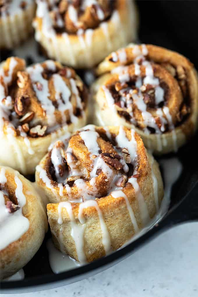 Close-up of glazed cinnamon rolls in a cast iron skillet.