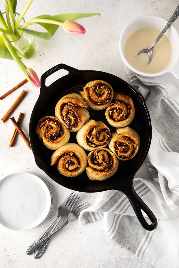Cinnamon rolls in a cast iron skillet beside a gray striped kitchen towel, a white bowl of glaze, cinnamon sticks, small round white plates, 3 forks and a vase with pink tulips.