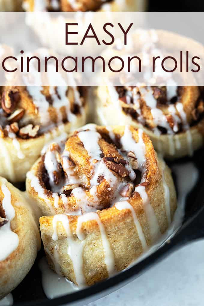 A close-up of glazed cinnamon rolls in a cast iron skillet.