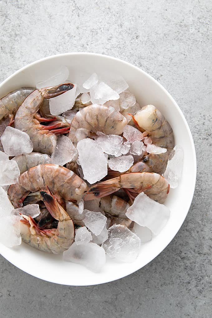 Fresh raw shrimp (unpeeled and headed) in a round white bowl with ice.
