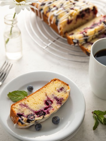 A slice of lemon blueberry bread on a round white plate with a sprig of mint, a white cup of coffee and 3 forks.