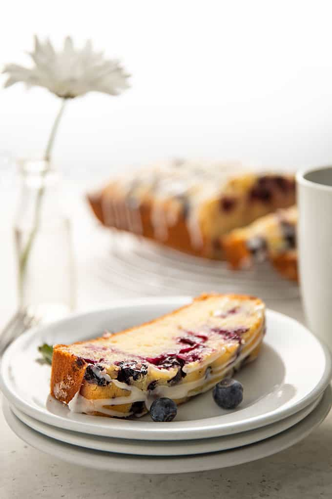 A slice of lemon blueberry loaf bread on a round white plate beside 3 forks and a white daisy in a small clear vase and a cup of coffee.