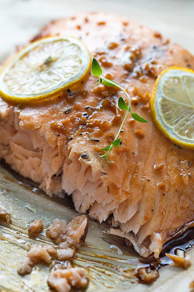 Maple glazed salmon topped with lemon slices and fresh thyme that has been sliced on a baking sheet.
