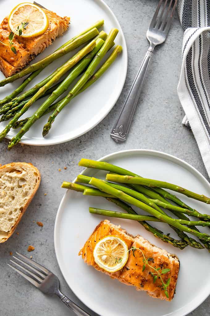 Maple glazed salmon and asparagus on 2 round white plates with a slice of French bread, 2 forks and a napkin.