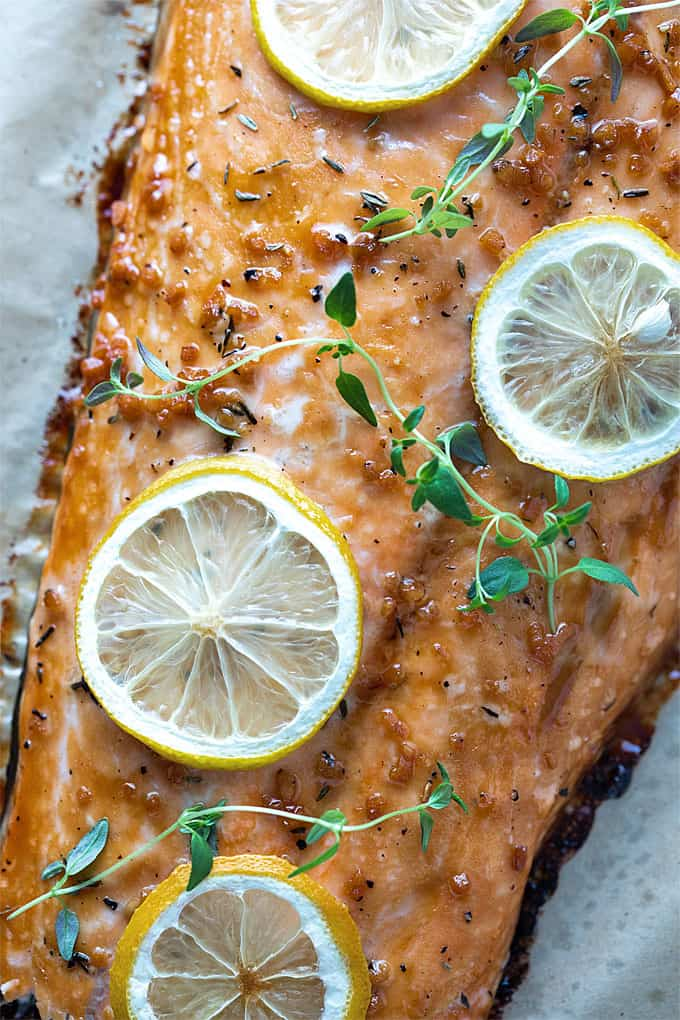 Maple glazed salmon filet topped with lemon slices and fresh thyme on parchment paper in a baking sheet.