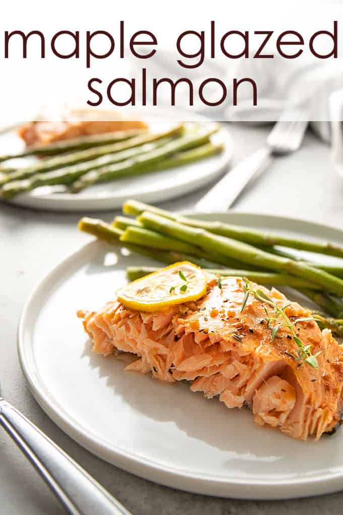 Maple glazed salmon topped with lemon slices and asparagus on a round white plate.