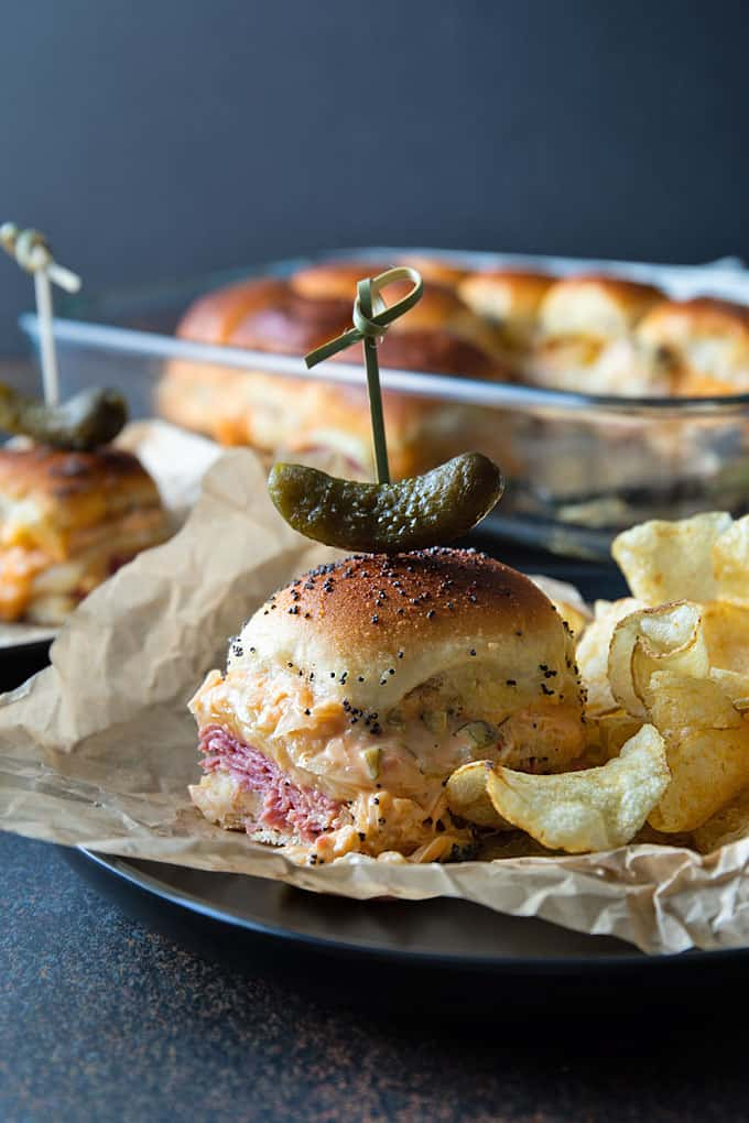 A reuben slider topped with a gherkin pickle and party pick with potato chips on a round black plate.