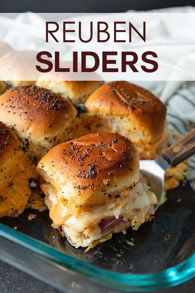 Baked Reuben sliders in a glass baking dish with a wooden-handle spatula beside a striped kitchen towel.