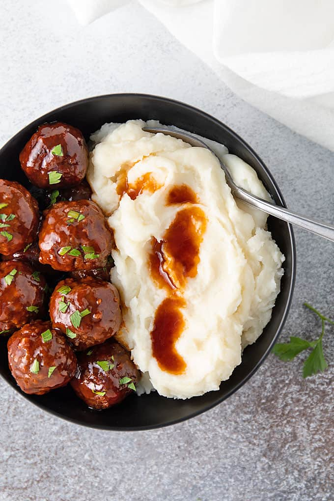 Bourbon meatballs topped with parsley and mashed potatoes in a round black bowl with a spoon.
