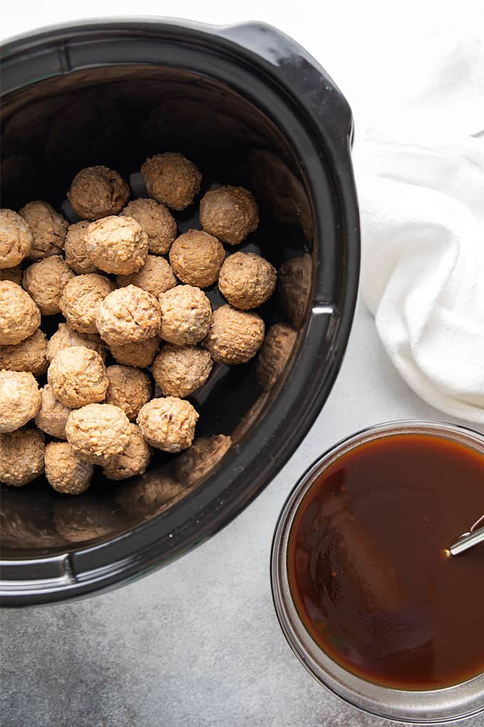 An oval slow cooker with meatballs beside a round bowl of bourbon barbecue sauce.