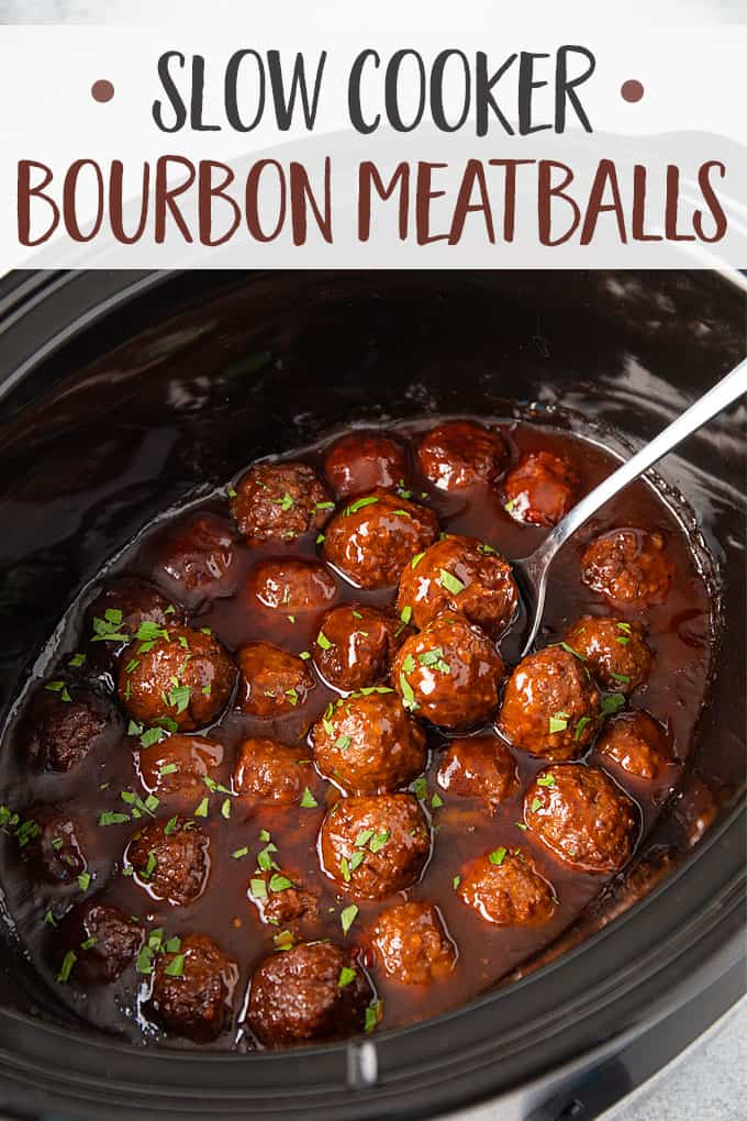 Bourbon meatballs sprinkled with fresh chopped parsley in a black oval slow cooker.