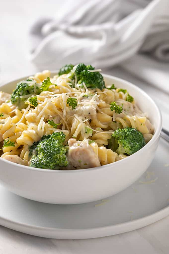Front view of Chicken and Broccoli Alfredo in a round white bowl beside a fork and white kitchen towel.