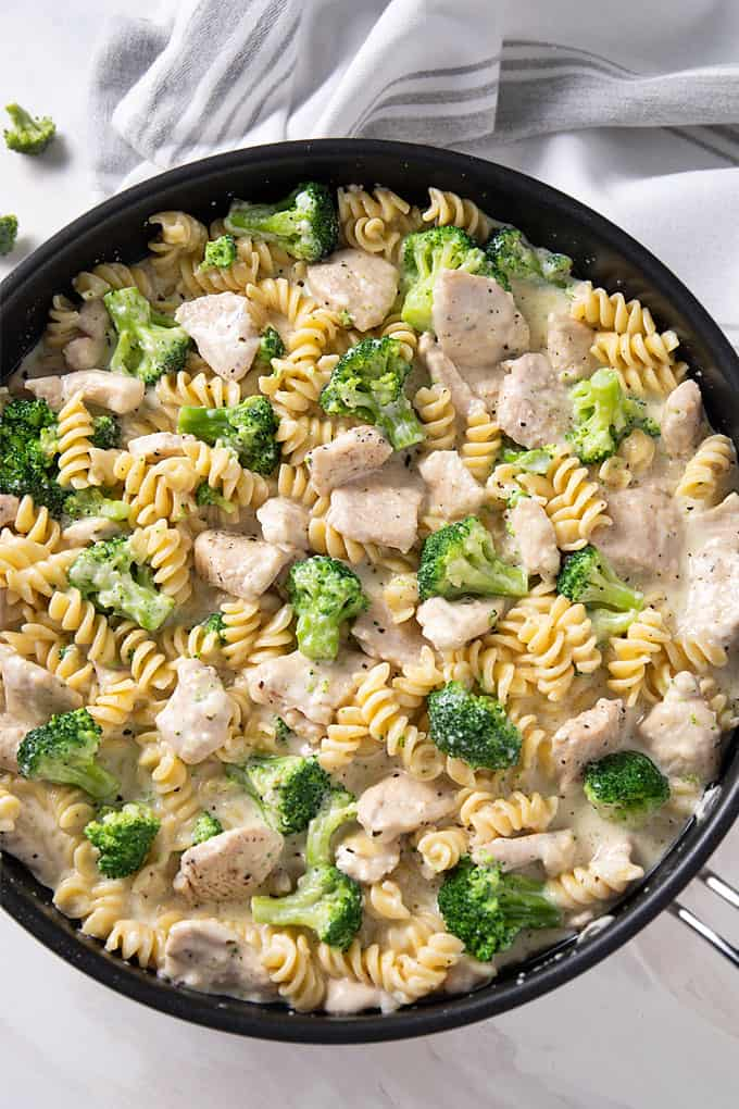 Overhead shot of Chicken and Broccoli Alfredo in a 12-inch skillet beside a white kitchen towel.