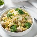 Chicken and Broccoli Alfredo in a round white bowl on a white plate with a fork on the right side.
