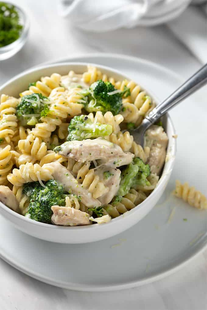 Overhead shot of a white bowl of chicken and broccoli Alfredo on a round white plate with a fork in the bowl.